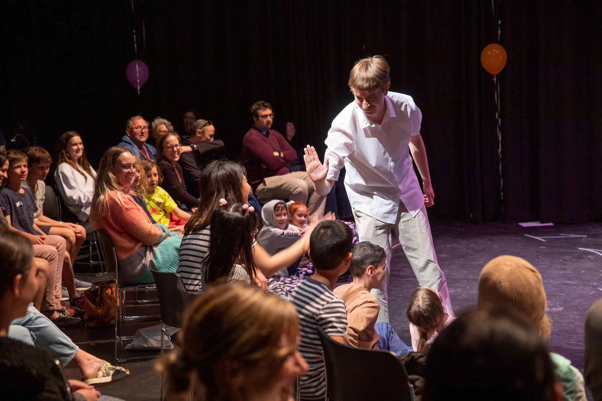 Smiling, Adam Kelly, the star of the show, gives audience members a high five